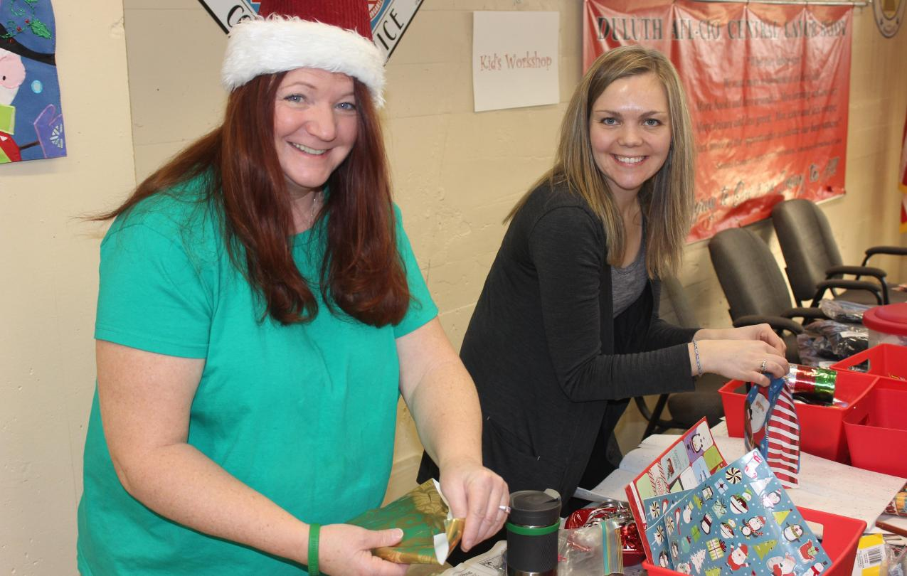 Christina St. Germaine, from Local 1092, helps Local 3558's Rachel Loeffler-Kemp prepare gifts for families at the AFL-CIO Community Services Program's annual kid's holiday party